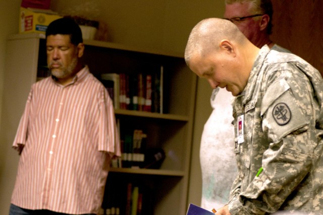 Chaplain (Capt.) Richard Dunbar, Warrior Transition Battalion, says a prayer during his weekly bible study at the Soldier Family Assistant Center on Sept. 12, 2012. Tony Melendez (left), of Chino, Calif., was a guest performer during the Bible study.