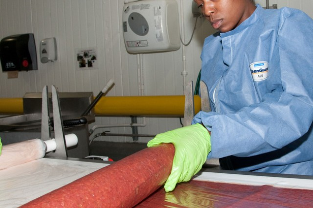 Stephanie Holmes, a food technician at the FPL Foods Cayce, S.C. processing plant, rolls a sheet of osomotically dehydrated meat product as it comes of the conveyor. FPL Foods has dedicated an area of its plant and members of its workforce, such as Holmes, in an effort to develop an array of innovative meat products.