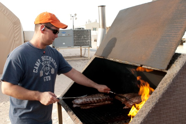 Spc. Joshua Long of the 4th Battalion, 118th Infantry Regiment, South Carolina Army National Guard barbecues ribs during the opening of the battalion's dayroom at Camp Buehring, Kuwait on Aug. 25. With the support of the battalion, Soldiers were able to scrounge amenities to create the dayroom as a social sanctuary away from the dust and heat of Kuwait. Long is from Charleston, S.C.