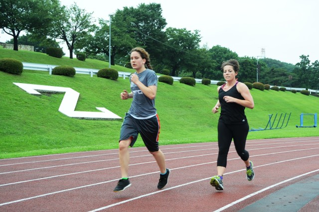 (From left): Second Lt. Kristen Harrison and Sgt. Penny Buzzella, both members of the U.S. Army Japan Ten-Miler team, run laps at the Zama American High School track as part of their training for the upcoming race. This year's team is comprised of four Soldiers from Camp Zama, Japan, and three from Okinawa.