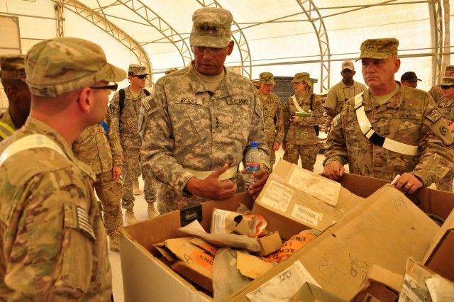 Lt. Gen. Vincent K. Brooks, Third Army/ARCENT commanding general, questions a Soldier on retrosort operations on September 17, 2012 at Kandahar Airfield. Brooks talked with Soldiers about their duties at the retrosort yard and asked them questions about current redeployment operations.