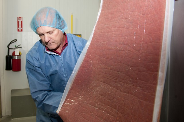 Randal Garrett, chief operating officer for FPL Foods, guides a sheet of osmotically dehydrated meat onto a conveyor belt at FPL Food's Cayce, S.C., processing plant. Garrett says the process will provide a number of potential meat products in many commercial markets.