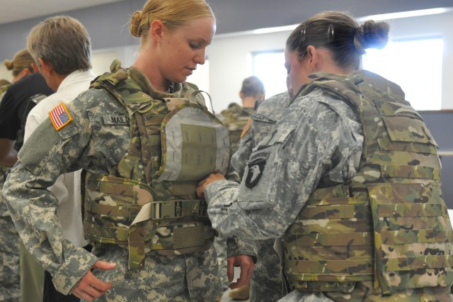 Spc. Arielle Mailloux gets some help adjusting her protoype Generation III Improved Outer Tactical Vest from Capt. Lindsey Pawlowski, Aug. 21, 2012, at Fort Campbell, Ky. Both Soldiers are with the 1st Brigade Combat Team Female Engagement Team, 101st Airborne Division (Air Assault). These prototypes were designed specifically for the needs of female Soldiers, with shorter torso length and other improvements.