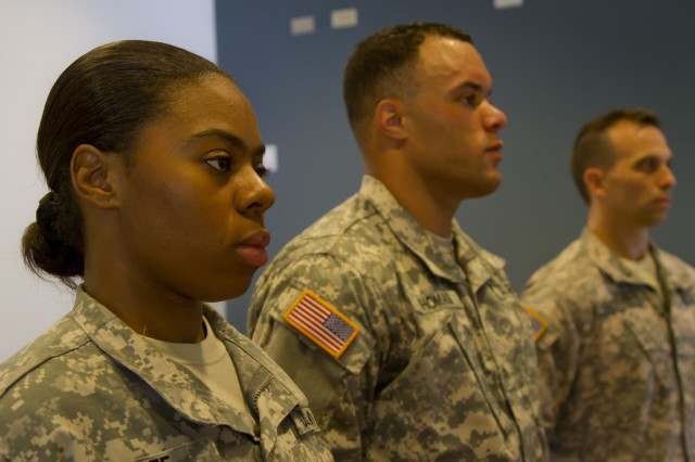 Pfc. Nikidia White paralegal specialist for the Headquarters Headquarters Company, 8th Special Troops battalion and Sgt. Thomas Sgt. Gary Thomas paralegal for the Headquarter Headquarters detachment, 500th Military Intelligence brigade, 8th Theater Sustainment Command stand for their award after winning the 8th Theater Sustainment Command paralegal warrior competition, August 30, 2012.