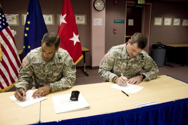 Maj. Gen. Michael Garrett, U.S. Army Alaska commanding general, and Col. Ronald Johnson, Fort Wainwright garrison commander, sign a memorandum of agreement extending a partnership between U.S. Army Alaska and the Fairbanks North Star School Borough, Sept 10, 2012, in Fairbanks, Alaska.