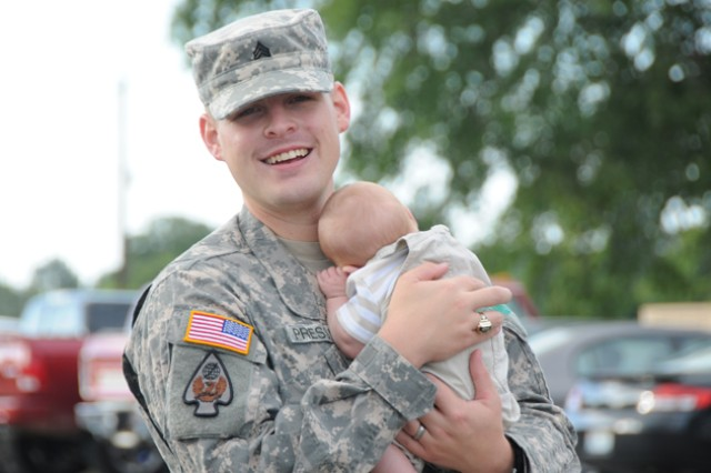 Sgt. Adam Pressley, HHC 164th Theater Airfield Operations Group, holds his newborn son during the 164th TAOG deployment ceremony at the U.S. Army Aviation Museum Sept. 15. Pressley deployed with about a dozen members of his unit to Afghanistan and Kuwait for a six-month deployment.