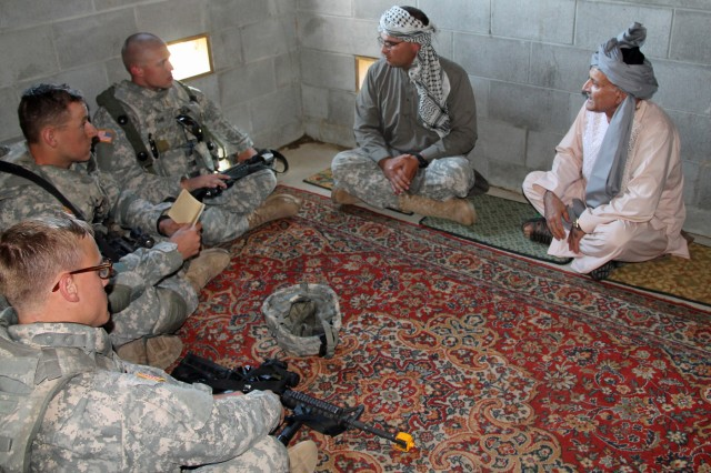 First Lieutenant Aaron Starr and other leaders with 6th Squadron, 8th Cavalry Regiment, 4th Infantry Brigade Combat Team, Third Infantry Division, speak Dari with an Afghan elder during a simulated key leader engagement, Sept. 10, on Fort Stewart, Ga.