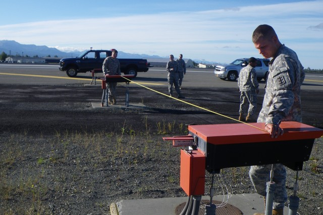 Sgt. Erik Stenslien (far left) and Sgt. Eric Rohr (far right), both technical engineers from the THS, HHC, 130th Eng. Bde., 8th TSC, measure the center of the navigational markers to determine the center of the object during a runway survey mission at Joint Base Elmendorf-Richardson, Alaska.