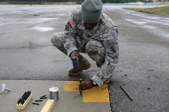 Sgt. 1st Class Dwight Hart, a technical engineer from the THS, HHC 130th Eng. Bde., 8th TSC, chisels away concrete to set a monument for a GPS control point during a runway survey mission at Joint Base Elmendorf-Richardson, Alaska.
