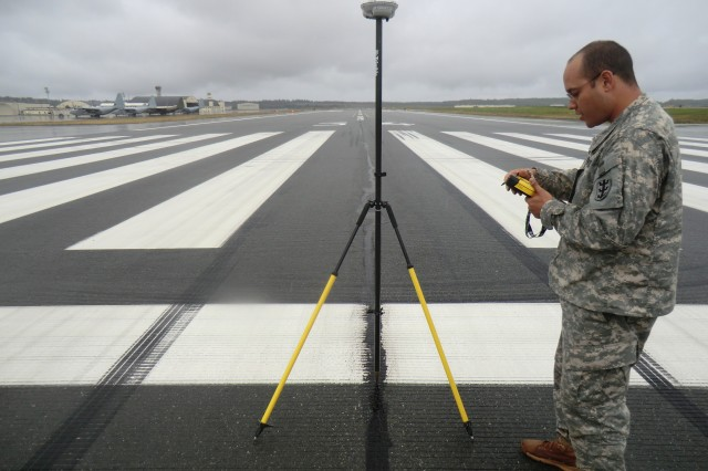 Spc. Daniel Nunez, a technical engineer from the THS, HHC 130th Eng. Bde., 8th TSC, configures a GPS to collect data on the center line of the runway at during a runway survey mission at Joint Base Elmendorf-Richardson, Alaska.