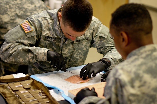 FORT DRUM, N.Y. - (left) Pfc. Zachary Pierret, a medic with the 1st Squadron, 89th Cavalry Regiment practices suturing on synthetic tissue at the Medical Simulation Training Center Sept. 12 while Spc. Carlton Clark looks on. The medical Soldiers are training in preparation for an upcoming rotation to the National Training Center at Fort Irwin, Calif. and eventual deployment to Afghanistan. Ten medics from the Wolverines attended the training. (Photo by Capt. Michael Greenberger)