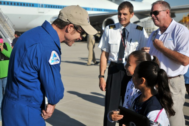 Bill Rieke, pilot of the modified Boeing 747-100 airliner transporting the Space Shuttle Endeavour across country, speaks to 9-year-old Reyna Paola and her 7-year-old sister, Andrea, as the shuttle stops to refuel at the Departure/Arrival Airfield Control Group at Biggs Army Airfield, Texas, Sept. 20, 2012. The shuttle was making its way across country to its final retirement home, the Californai Science Center in Los Angeles.