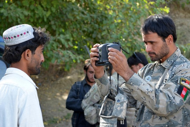 A member of the 3rd Zone Afghan Border Police takes a photo of a civilian during enrollment with the Handheld Interagency Identity Detection Equipment, a biometrics system, during Operation Southern Strike III in the village of Enjergay, Spin Boldak district, Kandahar province, Afghanistan, Sept. 3, 2012. The operation focused on dislocating the enemy from the local populations and connecting the district leadership with outlying villages.