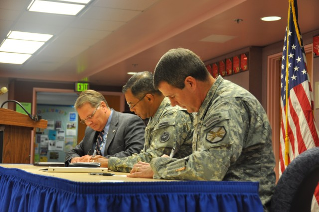 Pete Lewis (left), superintendent of schools for the Fairbanks-North Star Borough, Maj. Gen. Michael X. Garrett, the commanding general of U.S. Army Alaska and Col. Ronald M. Johnson, Fort Wainwright garrison commander, sign a memorandum of agreement extending the School Partnership Program.  The program gives Soldiers an opportunity to volunteer in the schools to work with students in traditional classes such as English and math, and also provides unique learning opportunities for students through field trips to Fort Wainwright. (Photo by Trish Muntean, Fort Wainwright PAO)