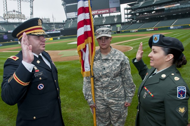 Specialist Reina Garay, a native of San Salvador, El Salvador, and an administration assistant with the 593rd Sustainment Brigade out of Joint Base Lewis-McChord, Wash., recites the Army oath of enlistment with her brigade commander, Col. Steven Fletcher, at Safeco Field in Seattle Sept. 19 during Garay's first reenlistment ceremony. Garay, an avid sports fan, chose to stage the event just behind the Mariners' home plate.
