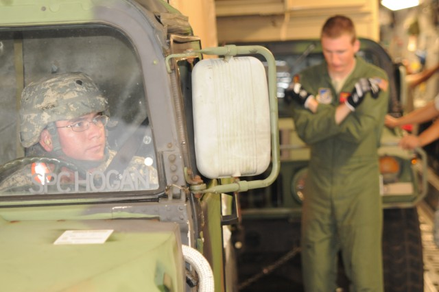 A Soldier with Operations Co., U.S. Army Pacific, watches the hand signals of an Air Force pilot as he loads a High Mobility Multipurpose Wheeled Vehicle into a C-17 at Joint-Base Pearl Harbor Hickam Sept. 21. The plane will carry equipment and Soldiers from the U.S. Army Pacific Contingency Command Post (CCP), 311th Signal Command and 25th Infantry Division to Talia Military Camp, Tonga where they will participate in Operation Coral Reef, a week-long combined, joint training exercise.