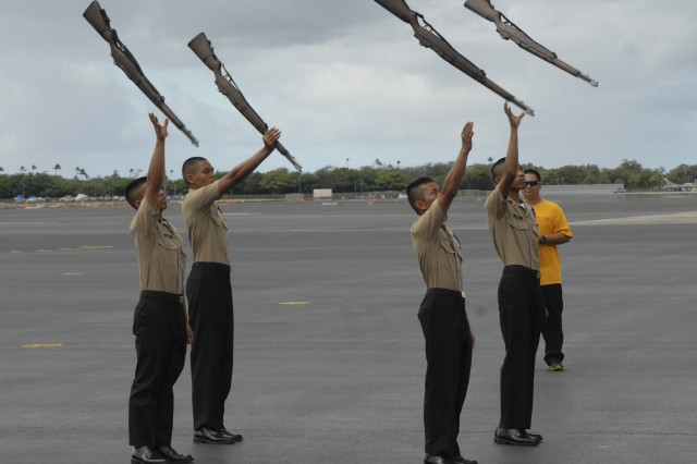 Cadets with Kalaheo High School throw their rifles into the air during the rifle drill portion of the Junior Reserve Officer Training Corps competition at Hickam Air Force Base, and hosted by the Sergeant Audie Murphy Clubs of Hawaii, the 25th Infantry Division, and Tripler Army Medical Center.