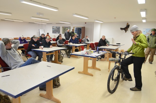 Recreation assistant Sara Baker explains the mechanics of a mountain bike to a group of Soldiers.