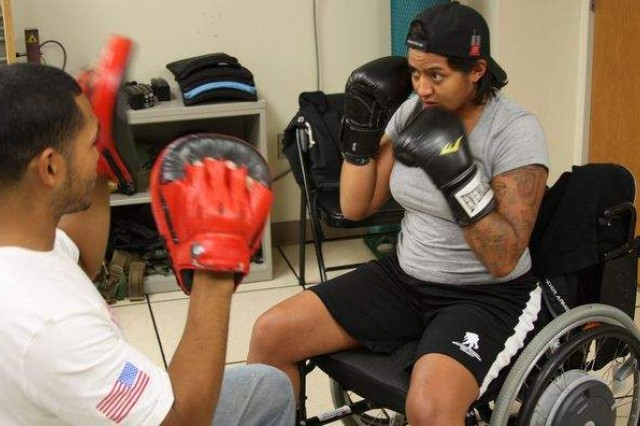 Boxing instructor and former Marine, Kelvin De La O works with wounded warrior Spc. May Agurto on her punch count and form during a recent training session at Walter Reed National Military Medical Center in Bethesda, Md. De La O and others hope that boxing can soon become an event in the next Paralympics.