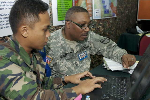Cpt. Muhamad Amir Hafiz, 7th Brigade Headquarters of the Malaysian Armed Forces, based in Mahkota Camp, Kluang, Johor, Malaysia and Master Sgt. Wilfred D. Robinson, Headquarters and Headquarters Company, 560th Battlefield Surveillance Brigade, work together during the Command Post Exercise portion of Keris Strike 12 in Camp Ulu Tiram, near Johor Bahru, Malaysia, Sept. 22. Keris Strike 12 is a U.S. Army Pacific sponsored Theater Security Cooperation Program exercise conducted annually with the Malaysian Armed Forces. Photo by Sgt. Edward Eagerton, 134th Public Affairs Detachment, Alaska Army National Guard.