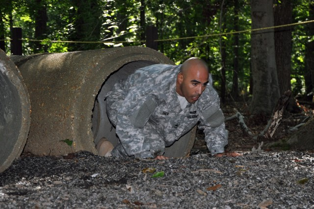 Sgt. 1st Class Aaron Baca, of the U.S. Army Intelligence Center of Excellence, crawls through a tunnel at the obstacle course as part of the 2012 Advanced Individual Training Platoon Sergeant of the Year competition, Sept. 25, 2012, at Fort Eustis, Va.. Baca serves at Fort Huachuca, Ariz., as an AIT platoon sergeant.