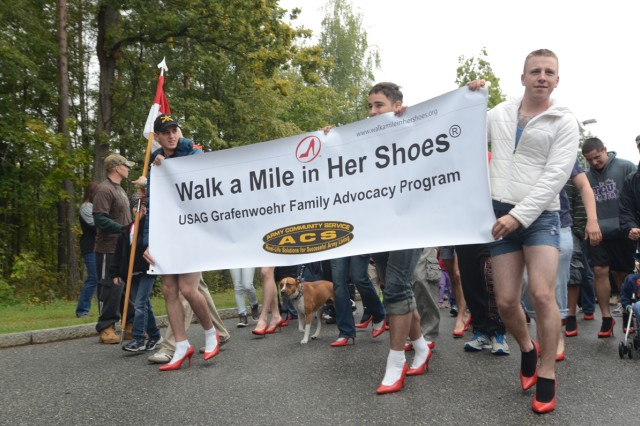 Participants strut down the lane donning red high heels in an effort to stand up against domestic violence at Rose Barracks, Sept. 22.