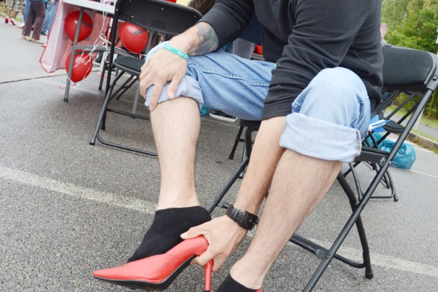 """Sgt. Cody Kincheloe, 44th Expeditionary Signal Battalion, woefully tries on his two-inch heels before """"Walking a Mile in Her Shoes"""" during the 2nd annual ACS-sponsored event known locally as """"Dudes in Heels."""""""