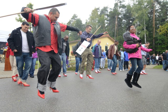 "Participants bust a move during ""Dudes in Heels,"" a local event tied to Walk a Mile in her Shoes, raising awareness for domestic violence and sexual assault."
