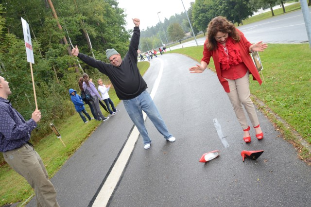 Sgt. 1st Class Jose Rivera, JMRC in Hohenfels, kicks of his heels at the finish line, much to the chagrin of ACS director Jolly Miller.
