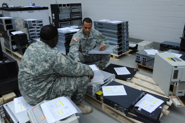 Sgt. Wayne D. Salas, a supply sergeant with the Special Troops Battalion, V Corps reviews his turn-in paperwork before handing it to the Spc. William J. Lewis, an automated logistics specialist with the 21st Theater Sustainment Command in Kaiserslautern, Germany.