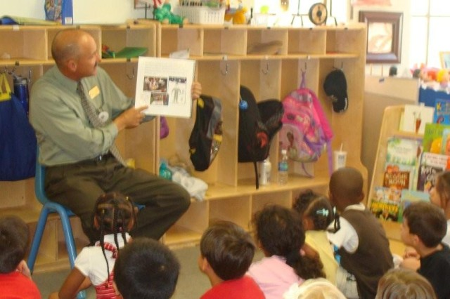 Tom Borer, deputy garrison commander, reads the Army Birthday story book to some children earlier this year at Child and Youth Services.