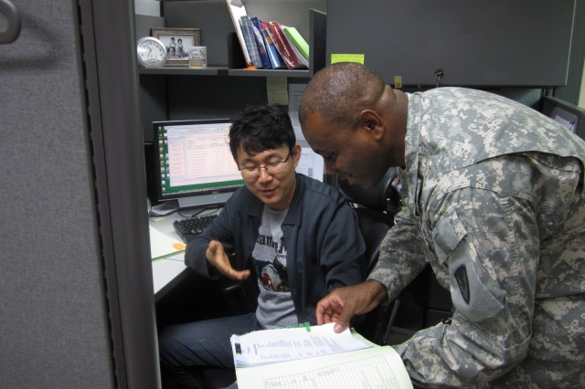 The 411th Contract Support Brigade's Staff Sgt. Elvon Dixon and Shu Song Yi review a procurement request for printers.