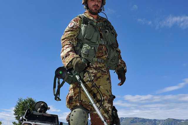 Italian Army soliders search for security threats during the Forward Engineer Support Training (FEST) route reconnaissance. The FEST allowed Europe District civilians and officers the opportunity to partner with foreign military to prepare for deployment.