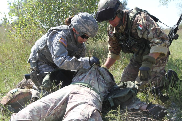 U.S. Army Corps of Engineers, Europe District employee Spc. Elizabeth Monge (left) administers medical attention to a simulated casualty of an Italian Army soldier alongside First Corporal-Major De Santa (right) during the FEST training.