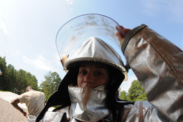 Pvt. Natalie Iori dons protective gear in preparation for her turn at putting out fires during training for the petroleum supply course at Firepit Training Area at Fort Lee, Va., July 23, 2012.  Iori was a part of class 041-12.