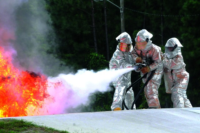An unidentified student, aided by an instructor on the left and another student on the right, aims a hose to put down a fuel fire at the Firepit Training Area at Fort Lee, Va., Sept. 6, 2012.  Students in kthe petroleum supply course undergo fire training in the eighth week of the 11-week 92F course.
