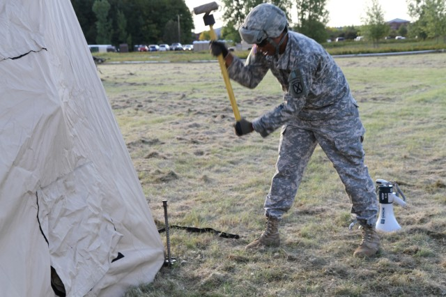 Pvt. Bryce Hill, infantryman assigned to Headquarters and Headquarters Battalion, 10th Mountain Division (LI), strikes a tent stake at Fort Drum's Sexton Field. Hill and other HHBN Soldiers prepare for the unit's command post exercise.