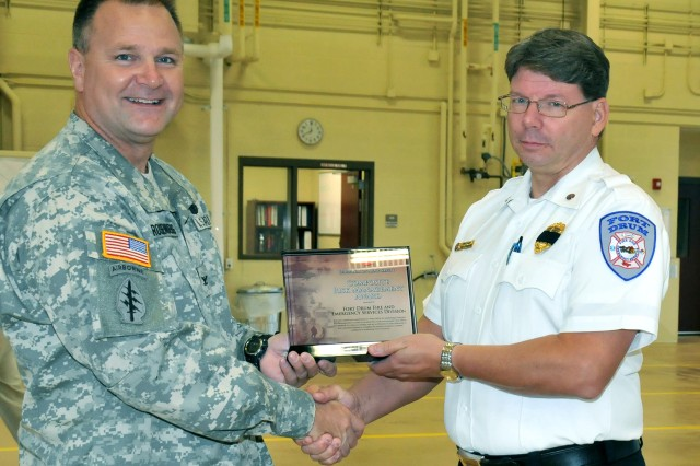 Col. Gary A. Rosenberg, Fort Drum garrison commander, presents Fort Drum Fire Chief Donald Striejewske with the Director of Army Safety Composite Risk Management Award during a brief ceremony Sept. 18 at Fire Station 2 on post.