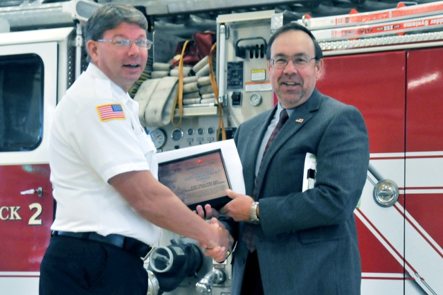 Joe Margrey, right, Fort Drum director of emergency services, congratulates Fire Chief Donald Striejewske last week after the post's fire department won the Director of Army Safety Composite Risk Management Award.