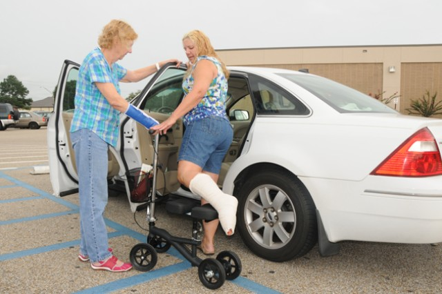 Delane Daniels, Family member, is helped into a car by Pauline Hobbs, military spouse, in a handicap parking space on post. A new plan calls for parking improvements in the form of more parking spots and less reserved spots.