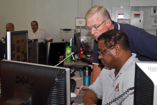 Kenny Steppe, standing, and Roy Stephens react to incoming information received over Stephens' computer in Anniston Army depot's Emergency Operations Center during an exercise to test the installation's emergency management capabilities.