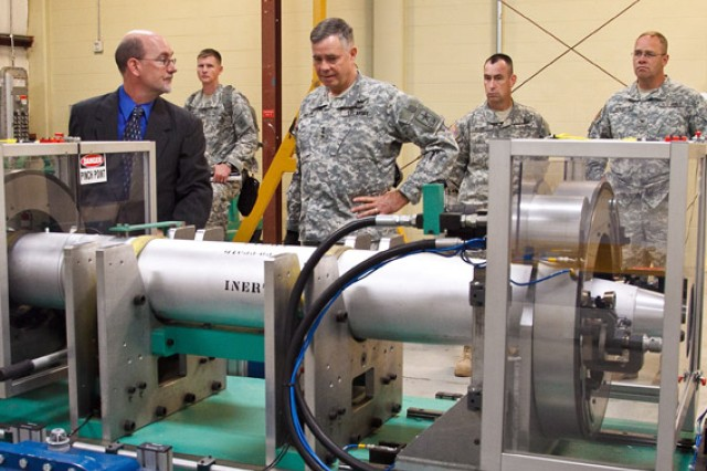 At an Anniston Munitions Center facility, Jeff Wright, chief engineer for Army Aviation and Missile Life Cycle Management Command G3 Missile Demilitarization, briefs Phillips on the demate equipment used on the Multiple Launch Rocket System.
