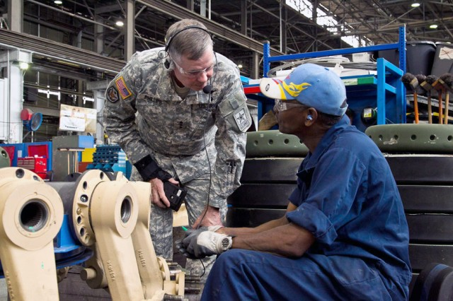Phillips speaks with Anniston Army Depot mechanic Julius Twymon in the depot's Combat Vehicle Repair Facility.