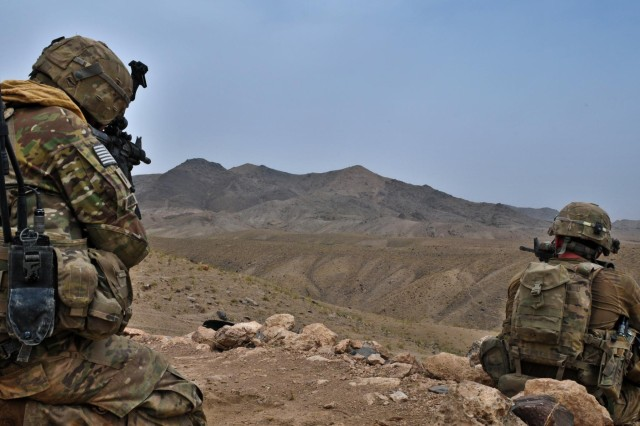 First Lt. Dillon Kareive (left), an officer with 426 Civil Affairs Battalion, Combined Task Force Arrowhead, and 1st Lt. Michael Hoffman, platoon leader of 2nd platoon Charlie Company, 5th Brigade, 20th  Infantry Regiment, watches for spotters in the mountains while providing security for Afghan National Army soldiers during operation Kalak Hode 5 in the Mizan District of southern Afghanistan, Sept. 5, 2012.