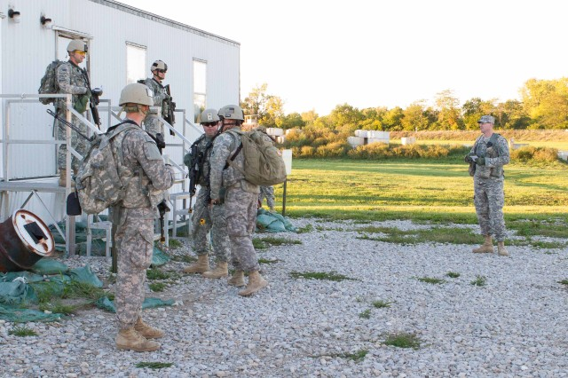 Sgt. 1st Class Wesley Averkamp, an observer, training with the 1-335th Infantry Regiment, 205th Infantry Brigade, watch as National Guard Soldiers from Kentucky's 2/138th Field Artillery Battalion, Lexington, Ky., preparing to secure a facility where recently freed hostages are being debriefed during a training exercise developed by the 205th Infantry Brigade at Camp Atterbury Joint Maneuvering Center, Ind., Sept. 22, 2012.