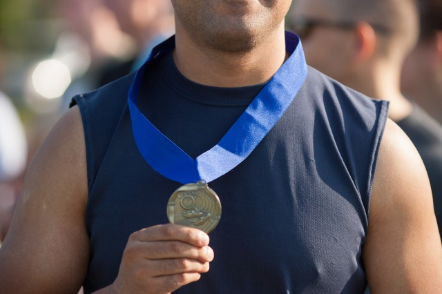 Luis Navarro of Columbia holds up his gold medal after finishing in first place the Football FanFare 5K Run on Saturday morning. Navarro's time of 17:41.9 beat the next closest runner by more than 40 seconds.
