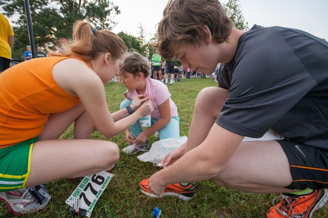 Rae Marquart and her children Olivia, 8, and Brandon, 14, of Ellicott City prep their race numbers and tie shoelaces before the 5K run around Burba Lake and down Rock Avenue.