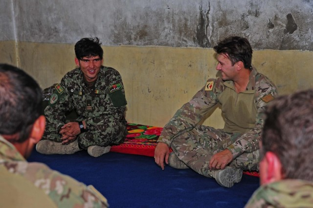 Australian Maj. Greg Colton, the commander of Mentoring Team Charlie, 3rd Royal Australian Regiment Task Group, shares a laugh with Afghan National Army 1st. Lt. Abdul Rahman at Village Stability Staging Area Anaconda, Khas Uruzgan district June 15, 2012. (Australian army photo by Cpl. Hamish Paterson)