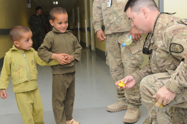 U.S. Air Force Lt. Col. John Savage, a Military Training Advisory Team mentor, hands small toys to children at Kandahar Regional Medical Hospital during women and children's day at the hospital on Camp Hero in Kandahar, Afghanistan, Sept. 25, 2012. KRMH is one of five hospitals of its kind in the country and specializes in treating Afghan National Army soldiers and Afghan police members.