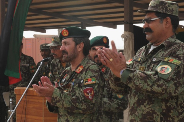 Maj. Gen. Abdul Hamid (left) commanding general of the 205th Hero Corp, and Col. Mohammad Haroon (right), Regional Military Training Center-South commander applaud new graduates at the center's graduation ceremony at Camp Hero, Afghanistan, Sept. 13, 2012. The center graduated more than 1,000 soldiers at the ceremony from both the basic training course and the officer basic course.
